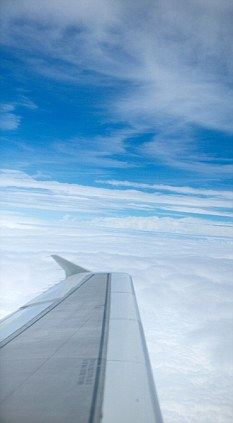 Airplanes wing in Blue sky with white clouds aerial from aeroplane aircraft