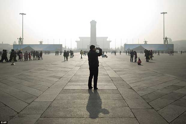 A tourist takes photos during a heavily polluted day on Tiananmen Square in Beijing, China, Thursday, Jan. 16, 2014