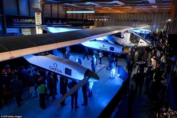 People look at the second Solar Impulse experimental solar-powered plane, the HB-SIB, to be used for a round-the-world voyage next year, during its presentation in Payerne on April 9, 2014.