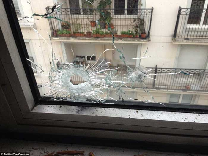 Targeted: A picture posted on Twitter reportedly showing bullets in one of the windows of the Charlie Hebdo offices